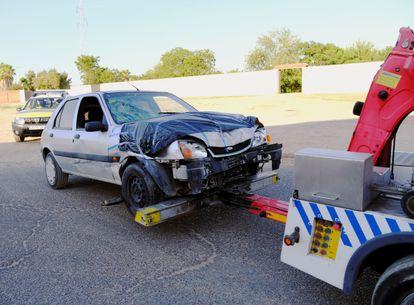 El coche con el que supuestamente una mujer ha atropellado a dos vecinos en una finca de Dos Hermanas, es sacado por una grúa de la finca.