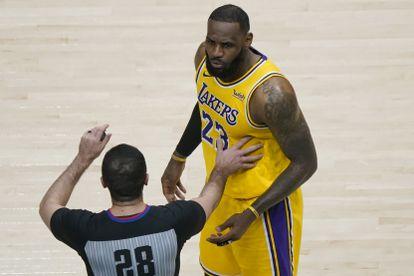 Uno de los árbitros separa a LeBron James de los aficionados con los que mantuvo una discusión durante el Hawks-Lakers.