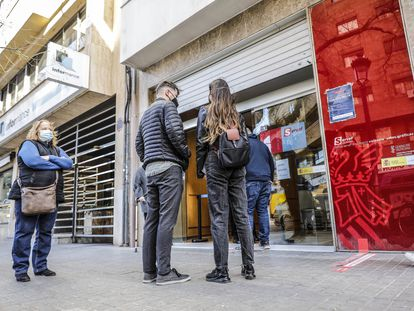 Varias personas hacen cola ante la puerta de oficina de empleo en València.