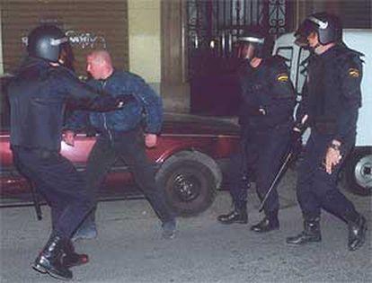 Tres policías rodean a un manifestante ultraderechista en Valencia.