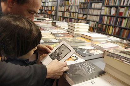 Usuarios de Kindle, <i>e-book</i> de Amazon, leen un libro electrónico en una librería de Madrid.
