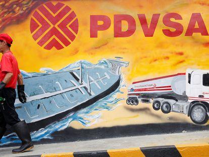 Un trabajador camina frente a un mural con el logo de PDVSA en Caracas, Venezuela.
