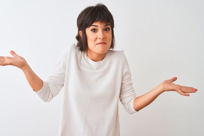 Young beautiful woman wearing casual t-shirt standing over isolated white background clueless and confused expression with arms and hands raised. Doubt concept.