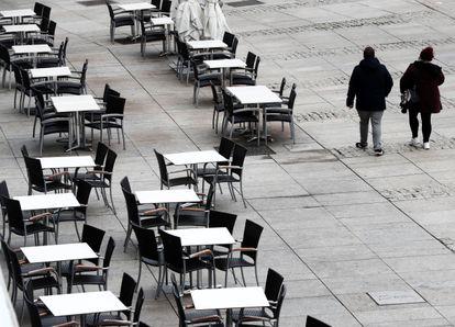 Dos personas caminan por una plaza del centro de Pamplona con las terrazas de las cafeterías vacías, el 22 de octubre.