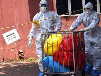 Personal médico con trajes protectores traslada objetos en bolsas del pabellón de infecciosos del Centro Médico Ernakulam en Kochi, Kerala (India), donde ha aparecido un brote del virus Nipah.