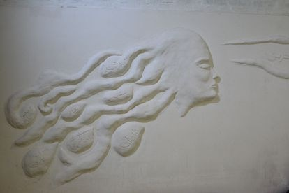 """Escultura fabricada por víctimas de violencia de género en Irak: una mujer mira hacia adelante, donde se lee la palabra que persigue: libertad. Sobre su melena lo que deja atrás. """"Cállate, vergüenza, no puedes porque eres mujer, prohibido salir""""."""