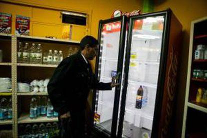 Un hombre abre una nevera mientras realiza compras en un abasto el 7 de junio de 2013, en Caracas. EFE/Archivo