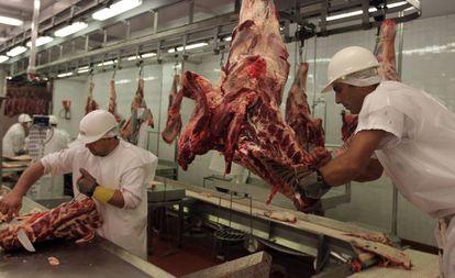 Dos trabajadores de una empacadora de carne en Montevideo.