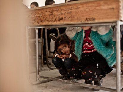 Nour se esconde debajo del pupitre al escuchar el paso de un helicóptero en una escuela clandestina de Alepo (Siria).