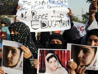 Activistas paquistaníes portan fotos de Malala en 2012, cuando la joven había sido víctima de un ataque talibán.
