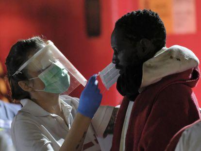 Los servicios sanitarios atienden a un grupo de inmigrantes llegados al puerto de Arguineguín (Gran Canaria) el pasado mes de abril.