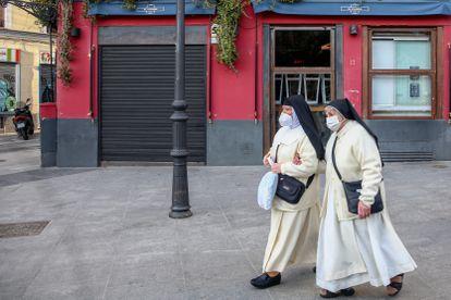 Dos monjas pasan por un restaurante cerrado en el distrito de La Latina, en Madrid, el 1 de febrero de 2021.