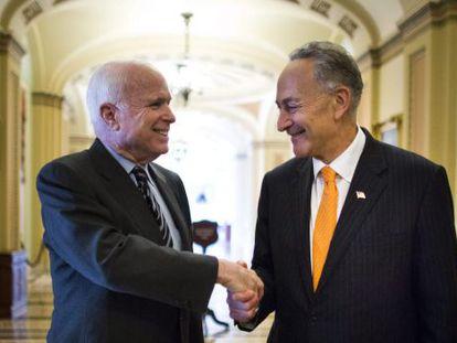 Los senadores John McCain (Izda.) y Charles Schumer se felicitan este jueves.