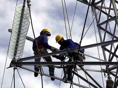 Dos operarios de Endesa trabajan en una torre de alta tensión para tratar de devolver la electricidad a Tenerife.