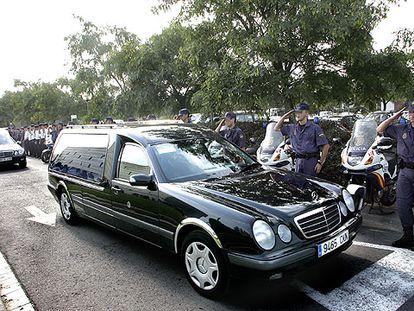 Miembros del Cuerpo Nacional de Policía saludan en L'Hospitalet a los coches fúnebres con los cadáveres de las dos agentes.
