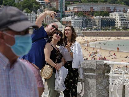 Un señor con mascarilla pasa por delante de un grupo de turistas que se fotografían en la playa donostiarra de La Concha.