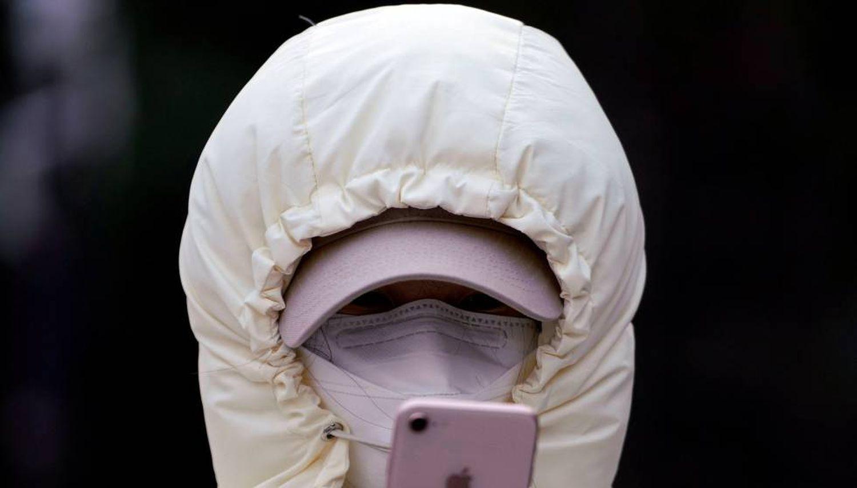 Una mujer con una máscara revisa su teléfono móvil.