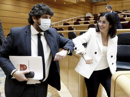El presidente de Murcia, Fernando López Miras, saluda con el codo a la ministra de Política Territorial, Carolina Darias, en la comisión de comunidades autónomas en el Senado.
