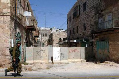 """Muro instalado en una calle de Hebrón para proteger a los colonos donde una pintada dice: """"Muerte a los árabes""""."""