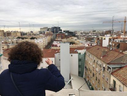 Silvia García, vecina de la calle Cartagena 118, muestra cómo se ve el local reformado y la chimenea industrial desde su azotea.