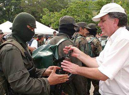 Un guerrillero entrega su arma a Luis Carlos Restrepo, alto comisionado para la paz de Colombia, en 2006.