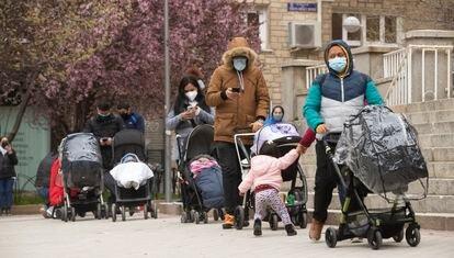Varias familias esperan en una cola del hambre en la Parroquia Santa Maria Micaela y San Enrique de Madrid.