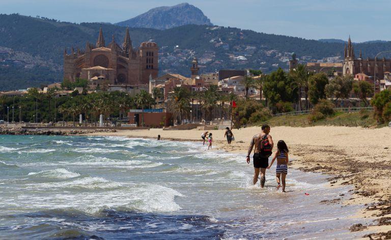 Varias personas disfrutan este sábado en una playa de Palma de Mallorca.