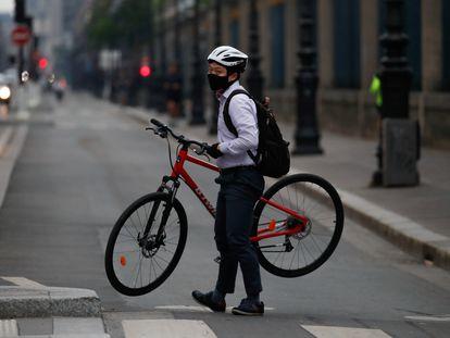 Un ciclista carga con su bicicleta en la calle Rivoli de París, en una imagen de mayo de 2020.