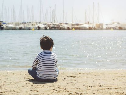 Un niño mira al horizonte.