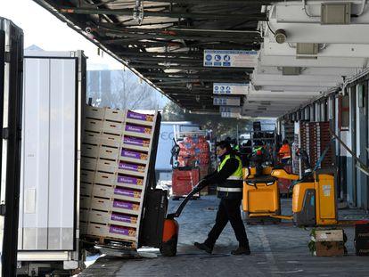 Descarga de los camiones repletos de frutas llegados a los hangares de Mercamadrid.