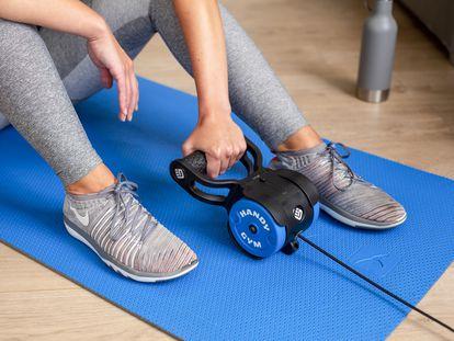 Imagen de una mujer entrenando con una máquina Handy Gym.