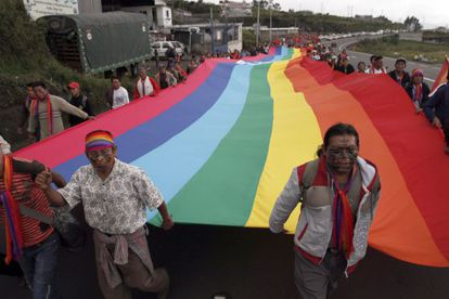 Indígenas ecuatorianos enarbolan la bandera de su comunidad en su marcha a Quito.