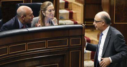 El ministro de Educación, José Ignacio Wert, conversa con el de Hacienda, Cristóbal Montoro, en el pleno del Congreso.