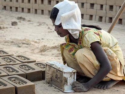 Una niña fabrica ladrillos en una población en India.