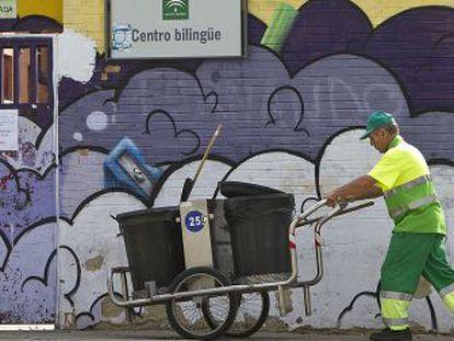 Un empleado del servicio de limpieza pasa frente al instituto afectado por una plaga en Jerez.