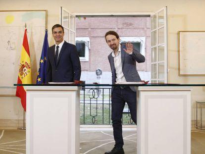 El presidente del Gobierno, Pedro Sánchez, firma con el secretario general de Podemos, Pablo Iglesias.