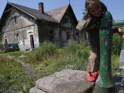 Una niña gitana recoge agua de una fuente en las afueras de la ciudad de Ozd, al noreste de Hungría.