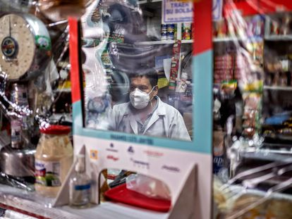 A seller waits for customers behind a protective nylon shield placed to prevent the spread of the new coronavirus, COVID-19, at Iztapalapa market, in Mexico City on June 22, 2020. - The spread of COVID-19 is accelerating across Latin America, with Mexico, Peru and Chile also hard-hit as death tolls soar and healthcare facilities are pushed toward collapse. (Photo by PEDRO PARDO / AFP)