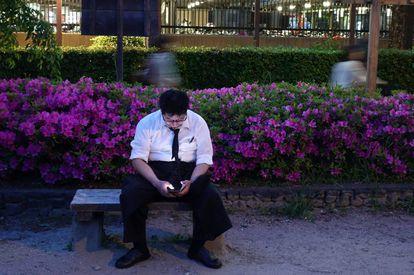 Un hombre mira su móvil sentado en un parque de Kioto, en 2018.