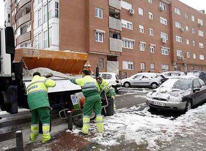 Operarios de limpieza echan sal para combatir la nieve en las calles de Madrid.