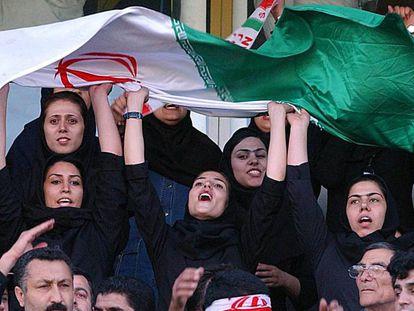 Varias mujeres ondean banderas de Irán en las gradas del estadio Azadí de Teherán, durante un partido de clasificación para el Mundial de Fútbol de Alemania 2006.