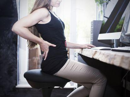 El dolor lumbar es uno de los más habituales entre quienes pasan mucho tiempo sentados frente al ordenador.