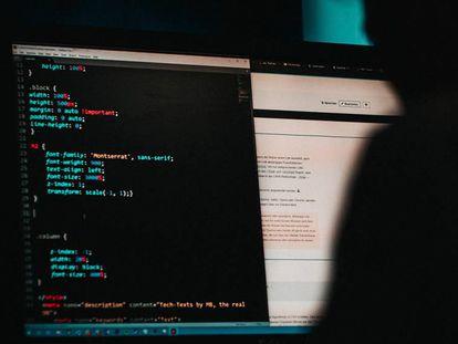 Un usuario introduce códigos en un ordenador.
