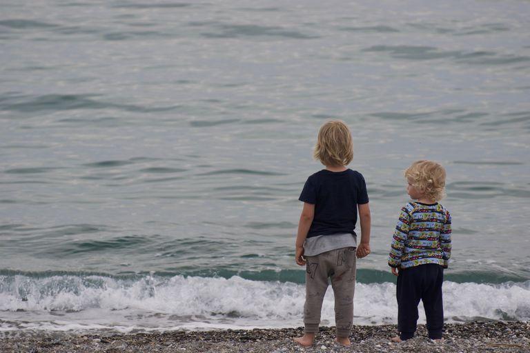 Dos hermanos están juntos en la playa.