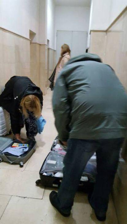 Varios turistas abren sus maletas en medio del portal.