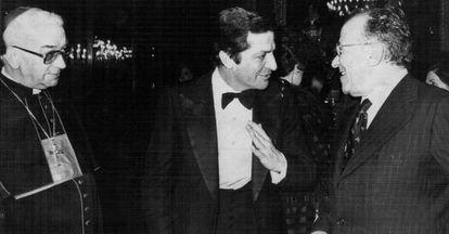El presidente del Gobierno, Adolfo Suárez, (centro) conversa con el secretario general del Partido Comunista, Santiago Carrillo, y el arzobispo de Madrid, Enrique Vicente y Tarancón, en una cela de gala en el Palacio Real el 14 de marzo de 1978.
