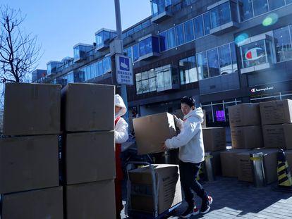 Dos trabajadores de una empresa de reparto en Pekín.