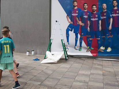 Un chico con la camiseta de Neymar pasa frente al nuevo póster sin el brasileño.