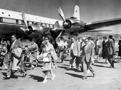 Pasajeros junto a un avión de Alitalia, en el aeropuerto de Ciampino, alrededor de 1964.