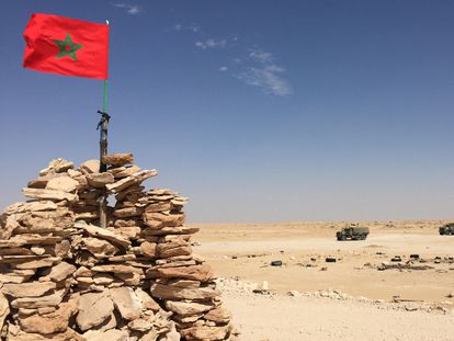Vehículos del Ejército marroquí pasan ante una bandera de Marruecos, en la zona del Guerguerat, próxima a la frontera con Mauritania, el pasado noviembre.